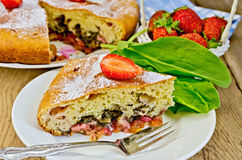 Pie with strawberry and sorrel on the board. A piece of sweet pie with strawberries and sorrel, napkin, pie, fork on the background of wooden boards Stock Photo