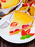 Pie strawberry with sour cream on dark board. A piece of strawberry pie with cream sauce, fork, strawberry, mint in white plate on a dark wooden board Stock Photo