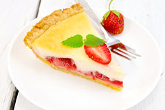 Pie strawberry with sour cream in dish on board. A piece of strawberry pie with cream sauce, fork, strawberry, mint in white plate on the background light wooden Royalty Free Stock Image