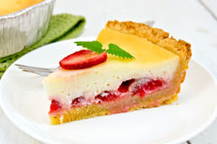 Pie strawberry with sour cream in dish on light board. A piece of strawberry pie with cream sauce, fork, strawberry, mint in white plate, napkin and shape with a Stock Photo