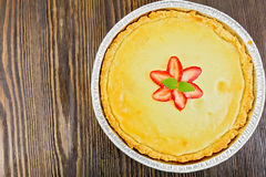 Pie strawberry with sour cream whole on board top. Strawberry cake with cream sauce, strawberry and mint in the form of foil on a dark wooden board on top Stock Photo