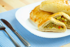 Pie stuffed with meat on a white plate and blue checkered tablec Royalty Free Stock Photo