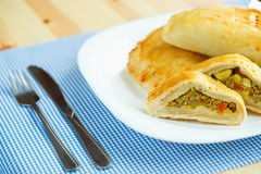 Pie stuffed with meat on a white plate and blue checkered tablec Royalty Free Stock Photography