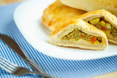 Pie stuffed with meat on a white plate and blue checkered tablec Royalty Free Stock Images