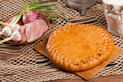 Pie on the table with food set. On wooden background Royalty Free Stock Images