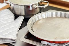 Pie or tart pan and oven glove in a kitchen. With a saucepan in the background ready for baking a recipe Stock Photos