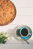 Pie with tea on a white wooden background.  Selective focus, toned image, film effect, top wiev. Pie with tea and snowdrops on a white wooden background Stock Images
