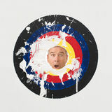 Pie throw game. A surprised man behind a circle target where you throw a pie at someones face Royalty Free Stock Image