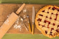 Pie with rolling pin on wooden surface. A pie on a wooden surface on a green table next to a rolling pin, some cutlery and some spilled flour royalty free stock image