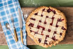 Pie with rolling pin on wooden surface. A pie on a wooden surface on a green table next to a rolling pin, some cutlery and some spilled flour Stock Photos