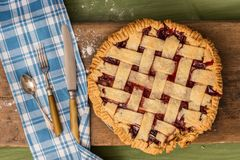 Pie with rolling pin on wooden surface. A pie on a wooden surface on a green table next to a rolling pin, some cutlery and some spilled flour Stock Image