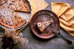 Pie on a wooden table. Baked cake in a ceramic form sprinkled with chocolate slices on a wooden table. rural style. still life. slice of cake Laid on clay plate Royalty Free Stock Photography