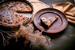 Pie on a wooden table. Baked cake in a ceramic form sprinkled with chocolate slices on a wooden table. rural style. still life. slice of cake Laid on clay plate Royalty Free Stock Photo