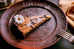 Pie on a wooden table. Baked cake in a ceramic form sprinkled with chocolate slices on a wooden table. rural style. still life. slice of cake Laid on clay plate Royalty Free Stock Image
