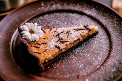 Pie on a wooden table. Baked cake in a ceramic form sprinkled with chocolate slices on a wooden table. rural style. still life. slice of cake Laid on clay plate Stock Image