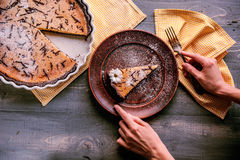 Pie on a wooden table. Baked cake in a ceramic form sprinkled with chocolate slices on a wooden table. rural style. still life. slice of cake Laid on clay plate Royalty Free Stock Images