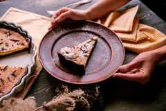 Pie on a wooden table. Baked cake in a ceramic form sprinkled with chocolate slices on a wooden table. rural style. still life. slice of cake Laid on clay plate Royalty Free Stock Photos