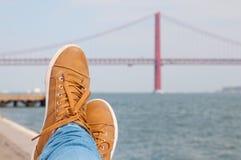 Pie zapatos Reclinación cerca del agua Opinión roja del puente de Lisboa en el fondo Imagenes de archivo