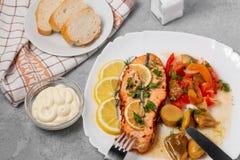 Piec łososia polędwicowy medalion z sałatką kiszeni warzywa i pieczarki na białym talerzu na szarym tle, odgórny widok, fotografia stock