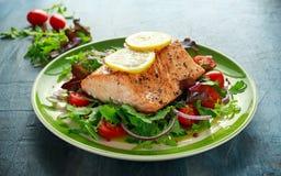 Piec łososiowy stek z pomidorem, cebula, mieszanka zieleń opuszcza sałatki w talerzu zdrowa żywność zdjęcia stock