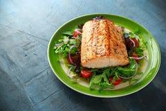 Piec łososiowy stek z pomidorem, cebula, mieszanka zieleń opuszcza sałatki w talerzu zdrowa żywność zdjęcia royalty free