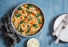 Piec bani i szpinaka spaghetti w smaży niecce na drewnianym stole, odgórny widok Wyśmienicie lunch w śródziemnomorskim stylu Zdjęcie Royalty Free