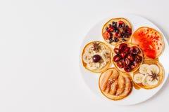 Piec bliny lub domowej roboty torty Na wierzchołku dekoruje z jagodami, owoc, miodem i dżemem na nieociosanym tle, Odgórny widok Fotografia Stock