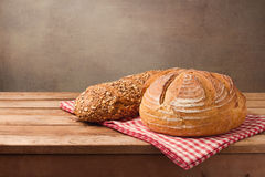 Piec chleb na drewnianym stole nad nieociosanym tłem Obrazy Stock
