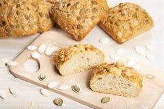 Piec chleb z dyniowymi ziarnami na tnącej desce obraz royalty free