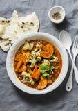 Piec currych warzywa Bataty, kalafior, marchewki, cebule, bania z curry'ego kumberlandem na popielatym tle, odgórny widok fotografia royalty free