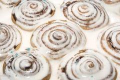 Piec cynamonowe babeczki nalewali z białym lodowaceniem namok fotografia royalty free