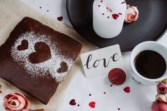 Piec domowej roboty kulebiak z sercem z świeczką dalej na białym tle i filiżanka kawy, zdjęcie stock