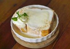 Piec gęsty chleb z rozciekłym masłem i miękkiej części śmietanką fotografia stock