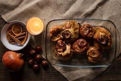 Piec jabłka w szklanej tacy z kasztanami, świeczką, cynamonem, pomarańcze i granatowem, zdjęcia royalty free