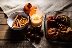 Piec jabłka w szklanej tacy z kasztanami, cynamonem, pomarańcze i granatowem, obraz stock