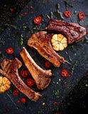 Piec jagnięcy cutlets ziobro z czosnkiem i ziele na kamiennym tle Fotografia Stock
