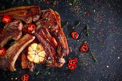 Piec jagnięcy cutlets ziobro z czosnkiem i ziele na kamiennym tle Zdjęcie Stock