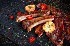 Piec jagnięcy cutlets ziobro z czosnkiem i ziele na kamiennym tle Zdjęcia Stock