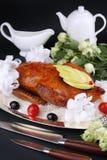 Piec kaczka faszerująca z jabłkiem, garnirującymi czereśniowymi pomidorami i oliwkami, Biel dekorujący położenie Zdjęcia Royalty Free