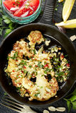 Piec kalafiorowy stek z dodatku upadem z arachidami, chili i świeżą pietruszką na żelaznej smaży niecce, obraz royalty free