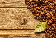 Piec kawowe fasole na textured nieociosanym drewnie Zdjęcia Stock