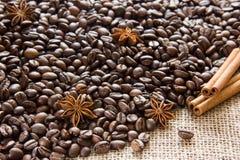 Piec kawowe fasole rozpraszają na parciaku z anyżowymi i cynamonowymi kijami Zdjęcie Royalty Free