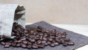 Piec kawowe fasole spada w stos kawowe fasole obok burlap worka zbiory wideo