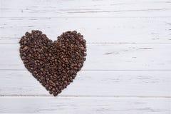 Piec kawowe fasole w formie serce na białym drewnianym backgrou Zdjęcia Royalty Free