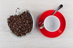 Piec kawowe fasole w pucharze, pusta filiżanka na spodeczku, łyżka Zdjęcia Stock