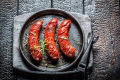 Piec kiełbasa z świeżymi ziele na gorącym grilla naczyniu Fotografia Stock