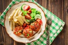 Piec klopsiki w pomidorowym kumberlandzie z francuskimi dłoniakami i sałatką Zdjęcia Royalty Free