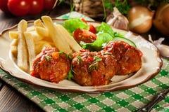 Piec klopsiki w pomidorowym kumberlandzie z francuskimi dłoniakami i sałatką Zdjęcia Stock