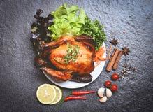 Piec kurczak, piec cały kurczak/piec na grillu na bielu talerzu z ziele, pikantność i ciemny tło zdjęcia royalty free
