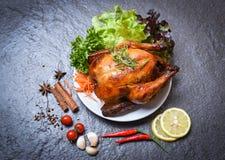Piec kurczak, piec cały kurczak/piec na grillu na talerzu z ziele, pikantność i ciemny tło obrazy royalty free